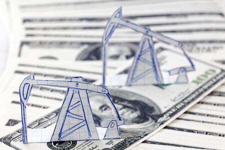 Petroleum pumpjack and oil rigs from paper on a heap of 100 dollar bills. Shallow focus. Concept image. Stock Photo
