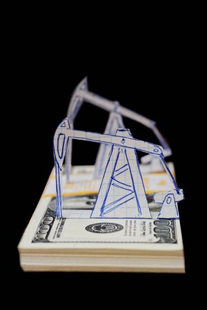 Petroleum pumpjack and oil rigs from paper on a pack of 100 dollar bills. Shallow focus. Isolated on black background.