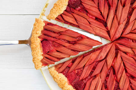 Homemade rhubarb and strawberry pie on white wooden table.