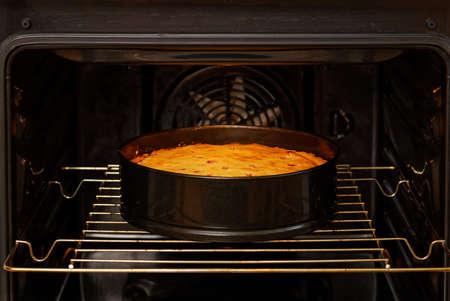Closeup homemade plum pie is prepared in the domestic oven.