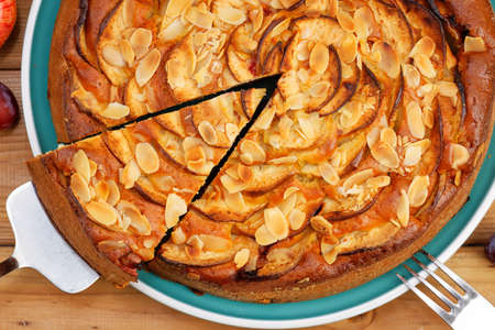 Close-up homemade pie with apples and plums with almond petals. Top view.
