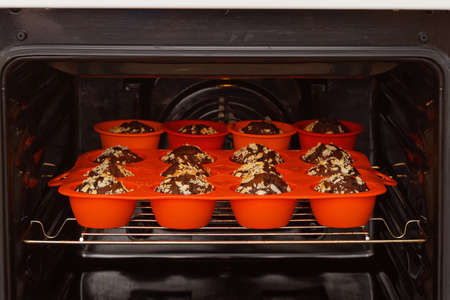 Chocolate muffins are baked in a red silicone mold inside a home oven. Shallow focus.