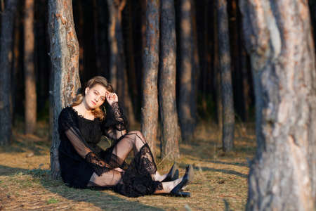 Portrait of a young beautiful girl in a black dress walking in the park. 免版税图像