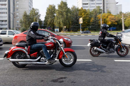 Ulyanovsk, Russia - September 26, 2020. Two motorcyclists ride a motorcycle among cars along a city street