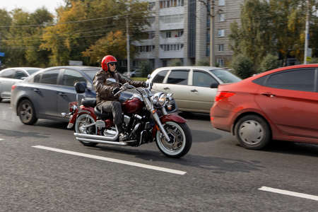 Ulyanovsk, Russia - September 26, 2020. Motorcyclist in a red helmet ride a motorcycle among cars along a city street