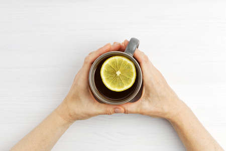 Female hands hold a warm cup of tea with a slice of lemon. Top view