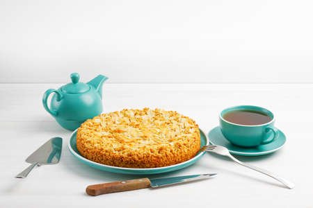 Apple pie with almond petals and cup of tea on white wooden table. Copyspace.