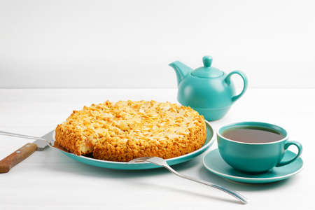 Apple pie with almond petals and cup of tea on white wooden table.