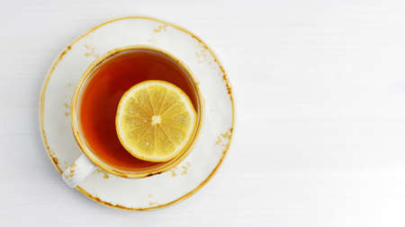 Cup of tea with a slice of lemon on white wooden table. Top view. Copyspace.