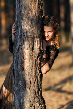 Girl in a black dress dress peeps out from behind a tree trunk in the park. Shallow focus. 免版税图像