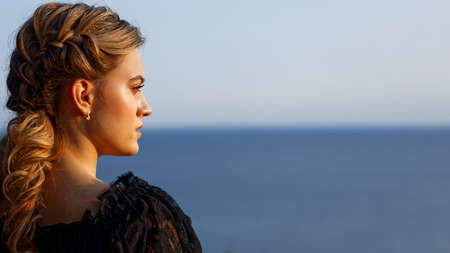 Portrait of a young beautiful looking into the distance on the background of the sea. Copyspace.