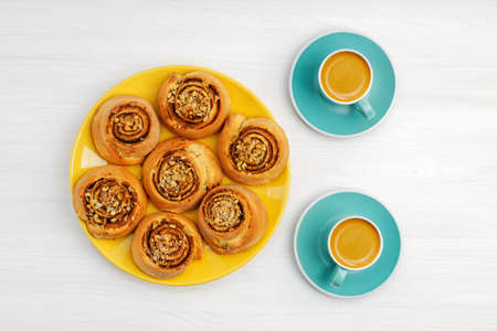 Homemade cinnamon rolls from yeast dough and two cups of coffee espresso on white wooden table. Top view. 免版税图像