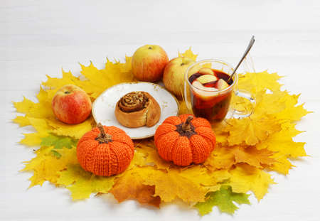 two toy knitted pumpkins, a cinnamon bun and a cup of mulled wine on a pile of yellow autumn leaves 免版税图像