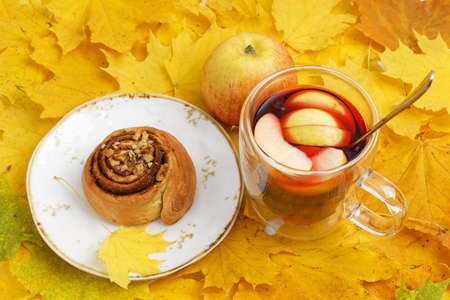 Homemade cinnamon bun and a mug of mulled wine on a pile of yellow autumn leaves