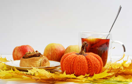 Homemade toy knitted pumpkin, a cinnamon bun and a mug of mulled wine on a pile of yellow autumn leaves. Copyspace. 免版税图像