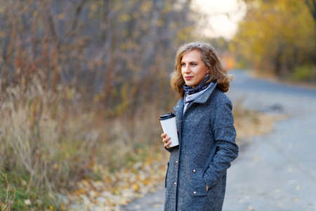 Portrait of a young woman with cardboard cup of coffee on the background of the road and autumn forest. Sahllow focus and blurred background.