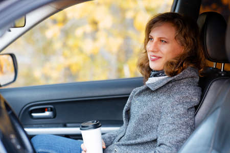 Woman with a cardboard cup of coffee sits on the passenger seat of a car. Shallow focus.