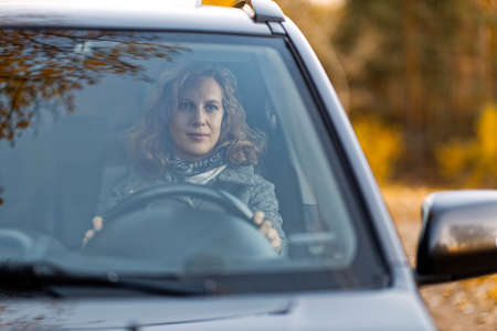Portrait of a woman sitting behind the wheel of a car on a background of autumn forest. Shallow focus.