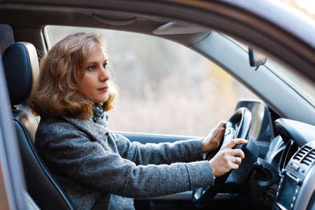 Portrait of a woman sitting behind the wheel of a car. Shallow focus.