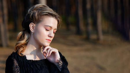 Portrait of a young woman standing with closed eyes on a forest background. Copyspace. Shallow focus.