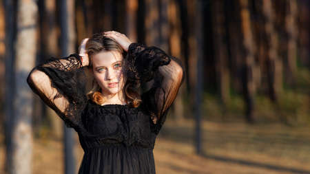 Portrait of a young beautiful woman in a black dress on blurred nature background. Copyspace. Shallow focus.