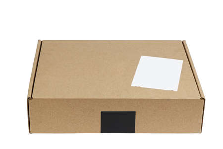 Closed brown cardboard box with blank white label. Box for parcel, delivery or packaging isolated on white background.