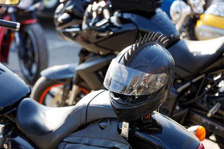 Closeup black moto helmet on motorcycle handlebars and motorbikes on blurred background 免版税图像
