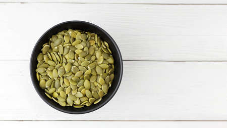 Pumpkin seeds in black bowl on white wooden table. Top view. Copyspace.