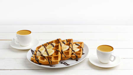 Homemade belgian waffles with banana slices topped with chocolate and two cup of coffee espresso on white wooden table. Copyspace. 免版税图像