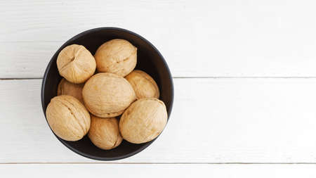 Walnuts in black bowl on white wooden table. Top view. Copyspace. 免版税图像