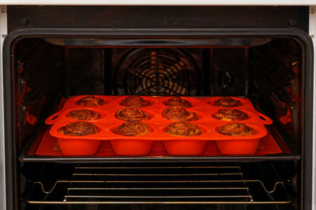 Homemade cinnamon rolls from yeast dough baked in a red silicone mold inside a home oven. Shallow focus. 免版税图像