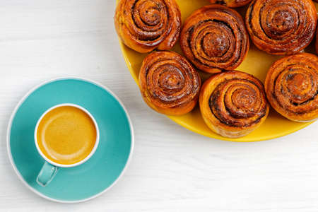 Homemade cinnamon rolls from yeast dough and cup of coffee espresso on white wooden table. Top view. 免版税图像