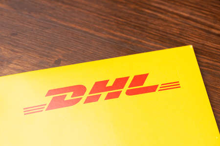 Ulyanovsk, Russia - October 27, 2020: Close-up yellow DHL envelope with red logo on wooden table.