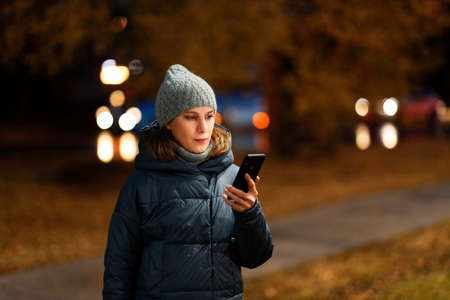 Outdoor portrait of young woman using her smartphone on night city. Shallow focus. Archivio Fotografico
