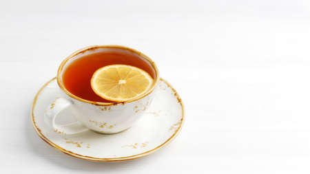 Cup of tea with a slice of lemon on white wooden table. Copyspace.