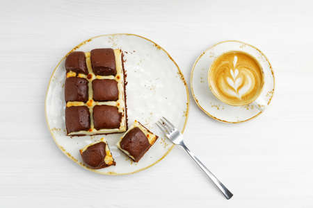 Homemade chocolate pie cheesecake and cup of coffee cappuccino on white wooden table. Top view.