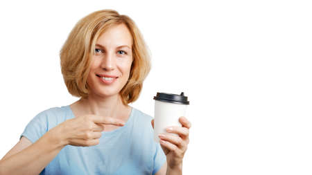 A smiling woman holds a cardboard cup in her hand and points to it with the finger of the other hand. Isolated on white. Copyspace. Archivio Fotografico