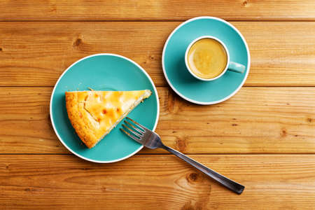 Piece of apple pie and cup of coffee espresso on wooden table. Top view. Archivio Fotografico
