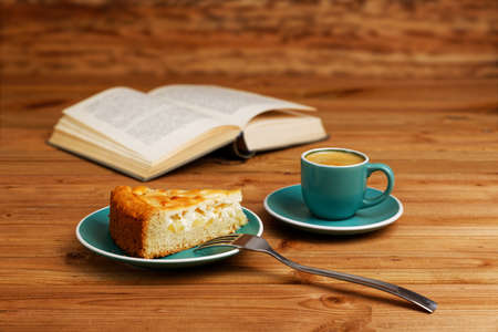 Piece of apple pie, cup of coffee espresso and open book on wooden table. Shallow focus.