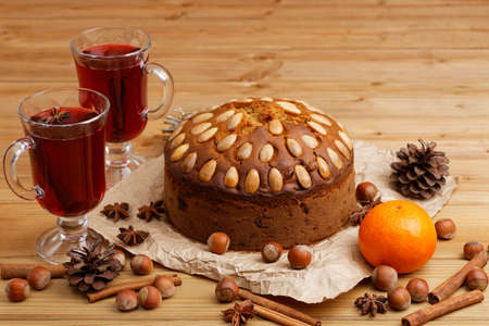 Homemade cake with almonds and two glasses with mulled wine on a wooden table