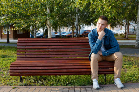 Young man sits on a park bench with a pensive look. Copyspace.