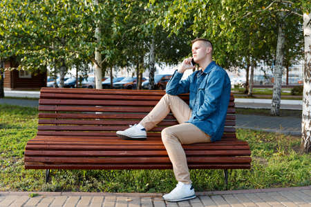 A young man sits on a park bench and talks on the phone with a pensive look. Copyspace. Archivio Fotografico