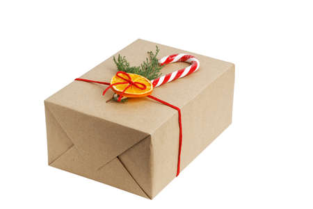 Gift box wrapped in kraft paper, tied with red twine and decorated with a juniper branch, orange slice and candy cane. Isolated on white. Archivio Fotografico