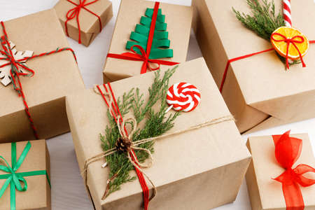 Group of gift boxes wrapped in kraft paper, tied with twine and decorated with a juniper branch, orange slice and candy. Archivio Fotografico