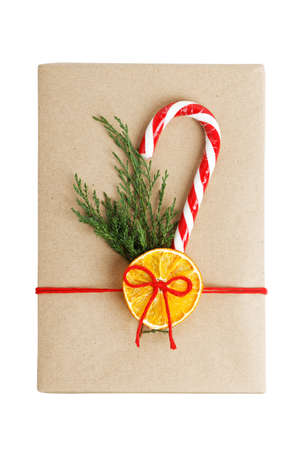 Gift box wrapped in kraft paper, tied with red twine and decorated with a juniper branch, orange slice and candy cane. Top view. Isolated on white.