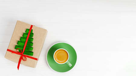 Cup of coffee and gift box wrapped in kraft paper, tied with red ribbon and decorated with a green ribbon in the shape of a Christmas tree on white wooden table. Top view. Copyspace.