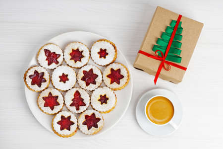Cup of coffee, homemade cookies and gift box wrapped in kraft paper decorated with a green ribbon in the shape of a Christmas tree on white wooden table. Top view.