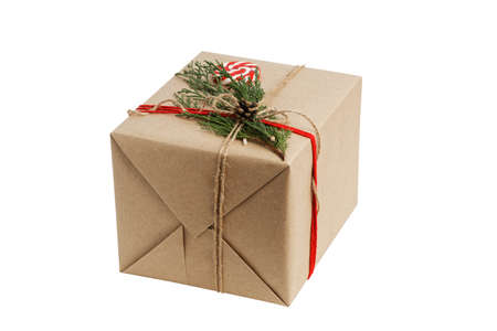 Gift box wrapped in kraft paper, tied with twine and decorated with a juniper branch and candy. Isolated on white. Archivio Fotografico