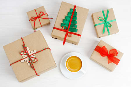 Group of gift boxes wrapped in kraft paper, tied with twine and decorated with a ribbons on white wooden table. Standard-Bild
