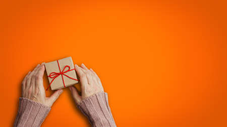 Female hands holding gift box wrapped in kraft paper and tied with red twine over orange background. Top view. Copyspace. Archivio Fotografico